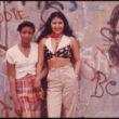 Denijs Lions (Lyon, Danny), Divas latīņamerikāņu meitenes pozē pie graffiti sienas Linča parkā Bruklinā, Ņujorkā (06/1974)
