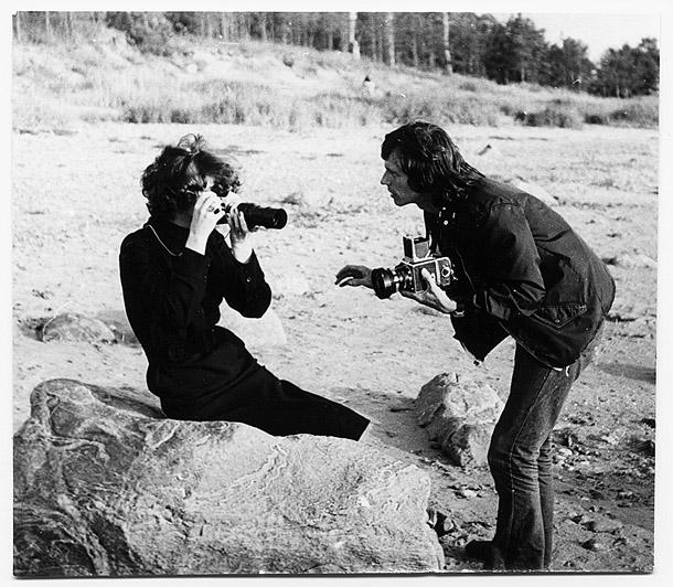 """Jānis Kreicbergs māca Rīgas Modeļu nama modelei Guntai pareizi turēt fotokameru. Top fotogrāfija Jāņa Kreicberga organizētās starptautiskās izstādes """"Fotografē sieviete"""" kataloga vākam. Foto - Ilga Sūna, 1976."""