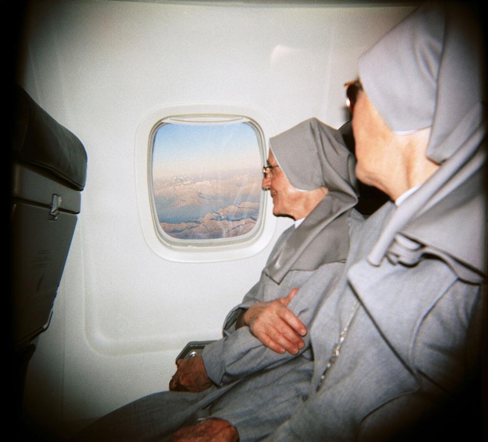 Kristofers Andersons. Mūķenes pa lidmašīnas logu vēro Alpu kalnus. Itālija, 2003