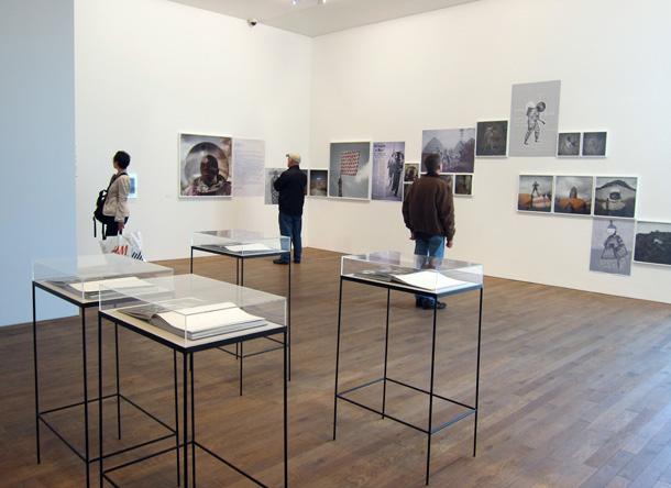 Skats no Deutsche Borse Photography Prize izstādes Londonā. Priekšplānā Brūmberga un Čanarina grāmatas, pie sienas - Kristīnes Demidelas grāmata izstādes formātā. Foto - Arnis Balčus
