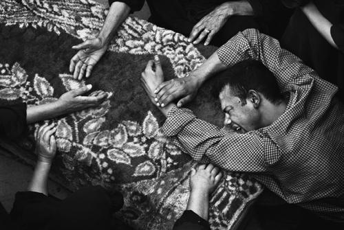 Jaunietis uz zārka sēro par sava drauga Ahmeda Šakera nāvi Irākā. Foto - Pols Hansens