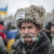 """Nikolijs Kudinovs, Rozbišivka Poltavas reģionā, 79 gadi. Uz manu jautājumu, par ko stāv – klusējot norāda uz uzšuvēm – """"Янукович - під арешт"""" (arestēt Janukoviču) uz jakas un """"Банду геть"""" (Bandu prom) uz cepures. Foto - Aleksejs Furmans"""
