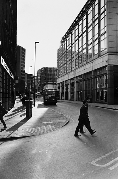 Mārtiņš Lablaiks. Pilsētas ainava ar diviem kopsolī ejošiem vīriešiem. Notingema, Anglija, 2009